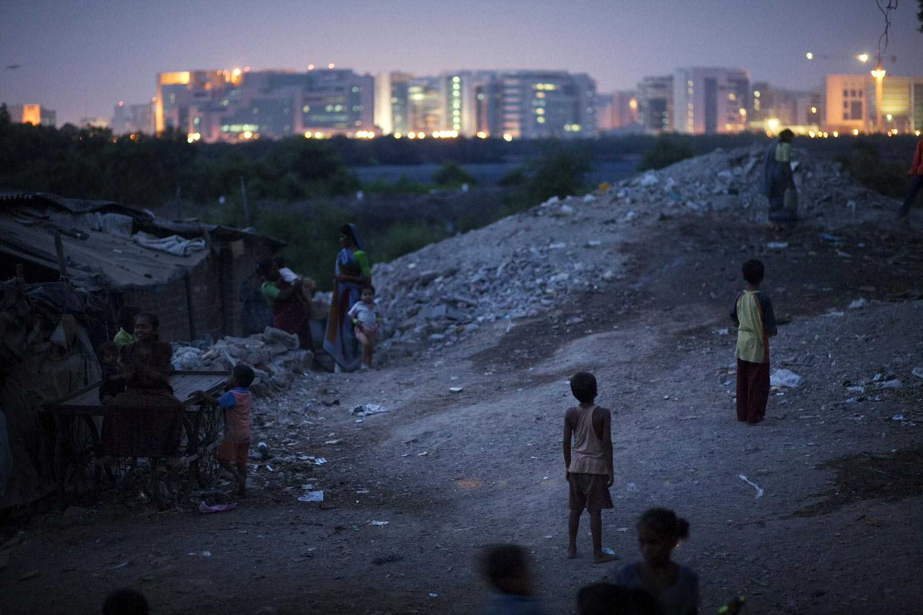 INDIA. Mumbai. 2006. From the edge of New Dharavi, children play by the shanties, with the new Bandra-Kurla Complex shining in the background. The BKC houses multinational companies and upscale offices, and is a high-profile project in Mumbai as the city reaches for a modern identity. Dharavi has become such a contentious issue in Mumbai politics partially because it is one of the few areas bordering the new complex. In between BKC and Dharavi is a mangrove swap and the Mithi River. Dharavi is one of Mumbai's biggest and longest standing slums. Home to somewhere between 600 000 and one million people, it is a beehive of recycling and manufacturing industries. However, Dharavi sits on prime real estate right in the heart of the booming megapolis, and is in close vicinity to the new Bandra-Kurla Complex, a new financial hub. Dharavi is now scheduled for redevelopment, meaning everything in the slum, for good and bad, is set to be demolished.