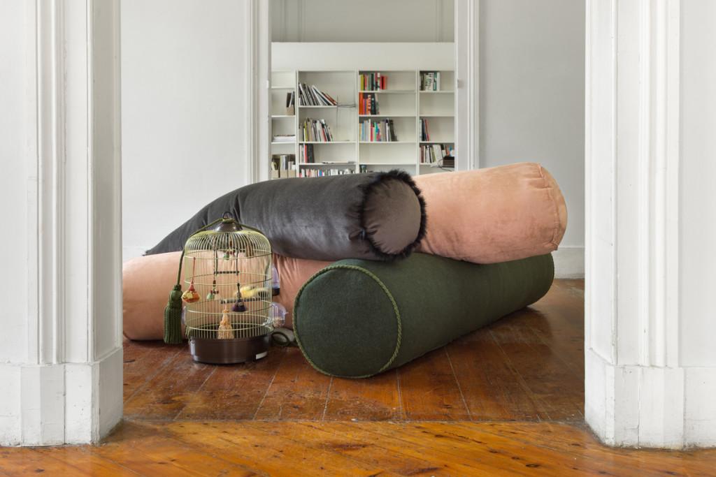 Patrizio Di Massimo, Mad, 2014, cuscino a rullo in lana verde con cordoncino, cuscino, a rullo in camoscio rosa, cuscino a rullo in velluto marrone con pelliccia di coniglio, gabbia per uccelli, canarino, tronchi, pietre, dimensioni variabili, Kunsthalle Lissabon, Lisbona, courtesy T293 gallery