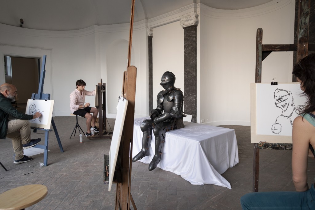 Self-portrait in armour (Take me I'm yours), 2018, Wood, cotton fabric, painting easels with stools, armour, drawing material, live model, Dimension vary with installation, Courtesy of the artist, ChertLüdde, Berlin and T293, Rome
