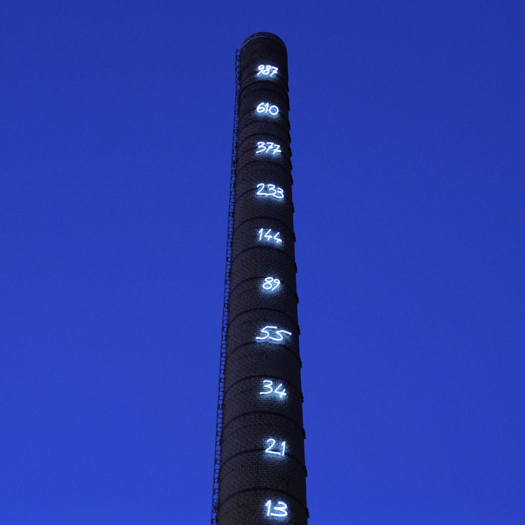 """Die """"Fibonacci-Reihe"""" des Lichtkünstlers Mario Merz restaurierten am Schornstein der ehemaligen Lindenbrauerei (Zentrum für Internationale Lichtkunst) in Unna am 4. Oktober 2012. Die Internetseite des Lichtkunstzentrums: """"Die Installation am Schornstein des Industriegebäudes ist sicherlichdie größte und bekannteste Arbeit (von Mario Merz).16 Zahlen, in der Handschrift des Künstlers angefertigt und an dem 52 Meter hohen Turm angebracht, leuchten in einem hellen Blau in den Himmel hinein. Die Zahlenfolge wird durch die Höhe des Schornsteins begrenzt und doch ist der Betrachter geneigt, die Reihe gedanklich fortzusetzen, was ihm jedoch nicht gelingen wird. So verkörpert das Werk von Mario Merz zwei gegensätzliche philosophische Gedanken: Die Natur auf der einen und das menschliche Streben nach Ordnung, nach Begrenzung und Vollkommenheit auf."""""""